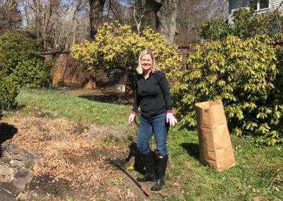 Meredith Hall Blonde Smiling Woman wearing pink garden gloves and rubber boots working on the restoration of the historic fletcher steel garden in Milton Massachusetts