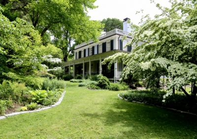 lush grass bordered with dogwood trees and shrubbery leading to a Brick home with black shutters