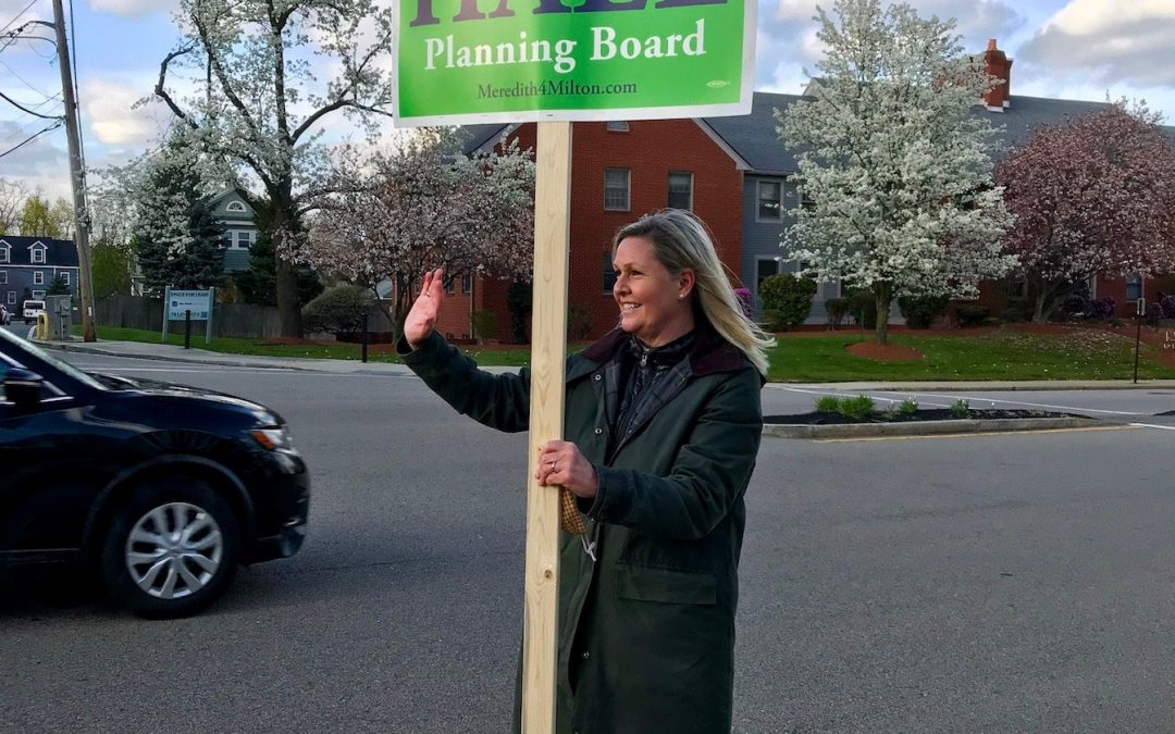 Meredith Hall holding a campaign sign and waving to constituents on election day