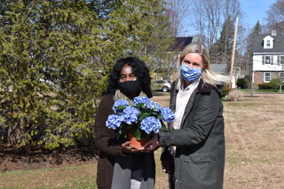 Meredith Hall and supporter standing in front of a large bush wearing masks and holding blue hydrengas